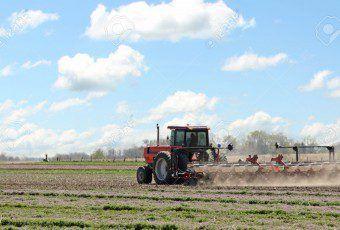 9641869-Tractor-tirando-una-sembradora-siembra-de-ma-z-en-un-campo-de-explotaci-n-Foto-de-archivo